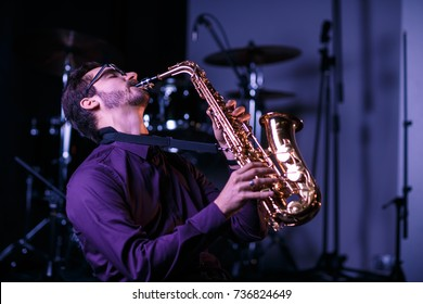 Musician playing enthusiastically on a stage
