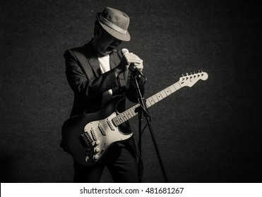 Musician playing the guitar with hand holding the microphone and singing on dark background,music concept