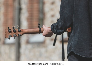 Musician playing guitar and singing outdoors - Shutterstock ID 1818453818