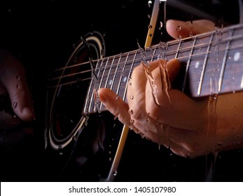 musician playing guitar at studio behind the glass with water drops