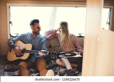 musician playing on acoustic guitar while girl looking at him and holding vinyl record inside campervan