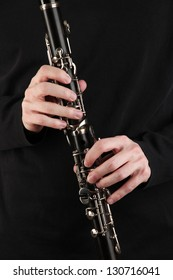 Musician playing on clarinet on black background