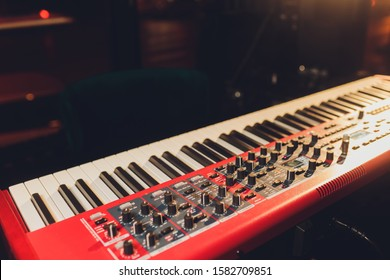 Musician playing on the keyboard synthesizer piano keys. Musician plays a musical instrument on the concert stage.