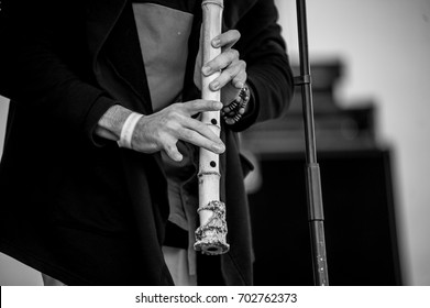 Musician playing on a wooden flute, black & white