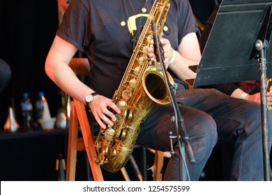 Musician playing saxophone at live concert on the stage