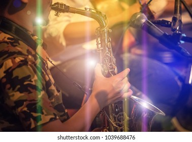 musician playing the saxophone on band in nigh concert