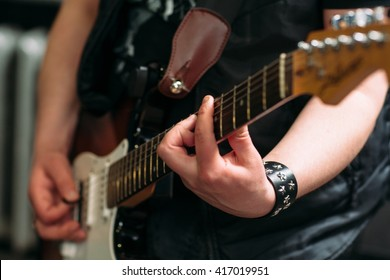 Musician playing six string electric guitar in sound recording studio. Rocker playing on electric guitar, closeup. Musical instrument closeup.
