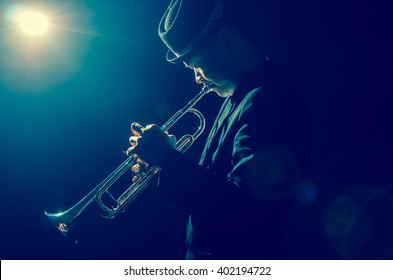 Musician playing the Trumpet with spot light and len flare on the stage