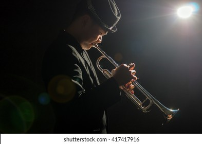 Musician playing the Trumpet with spot light and lens flare on the stage
