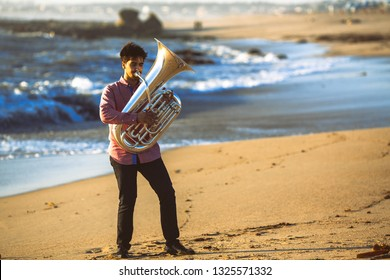Musician playing the Tuba on the Ocean coast.