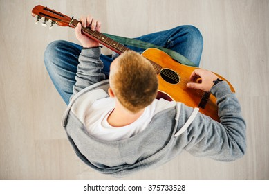 Musician plays Acoustic Guitar, Bird-Eyes View. Focus on Guitar