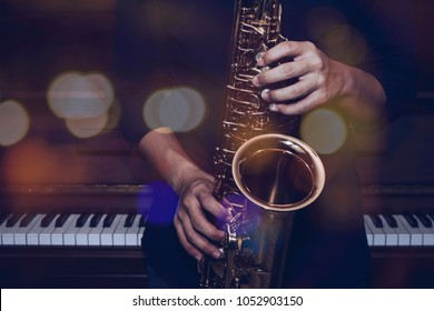 musician plays alto saxophone over piano with Bokeh light  background