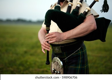A musician plays the bagpipes in the fields. Fingers and bagpipe close up.