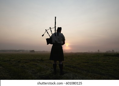 A musician plays the bagpipes in the fields at sunset.