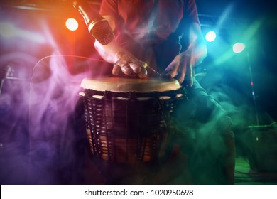 The musician plays the bongo on stage. Stage light. Smoke.