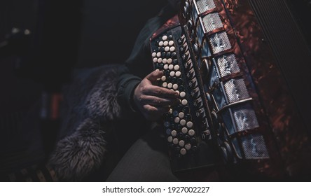 The musician plays the button accordion in the studio. The concept of music recording or music rehearsal.