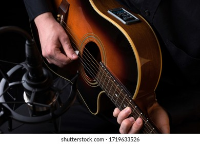 Musician Plays an Electric-Acoustic Guitar in a Recording Studio with a Microphone