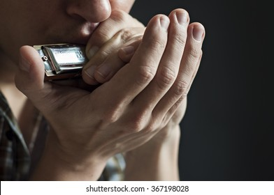 Musician plays the harmonica on black background
