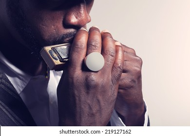 musician plays the harmonica on white background