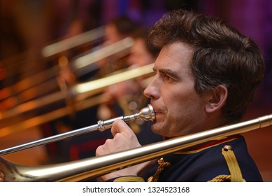 A musician plays his slide trombone in the brass band during a live concert performance