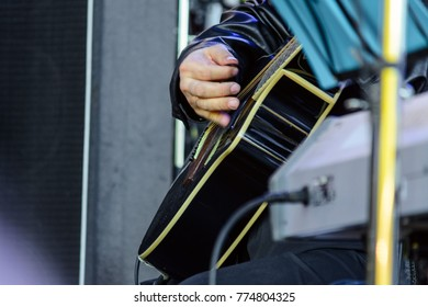 The musician plays on a black guitar.