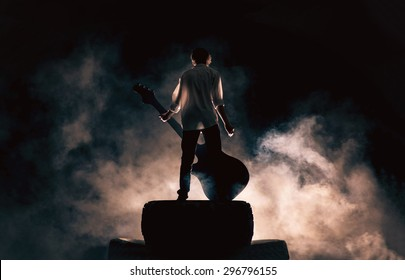 The musician plays on a large rock guitar in a great smoke, rock music, concert and festival