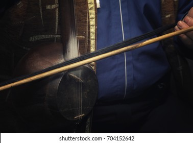 the musician plays on a traditional Middle Eastern and Asian stringed musical instrument