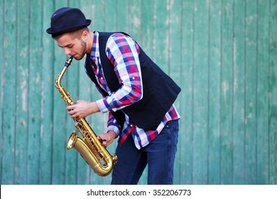 The musician plays saxophone on green wooden background