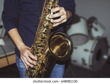 musician plays tenor saxophone on stage with blurred music instrument background