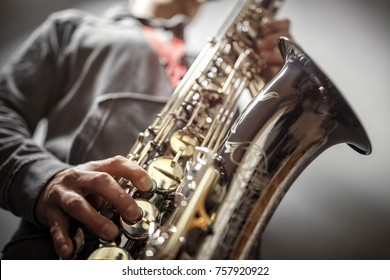 Musician or saxophonist playing a saxophone