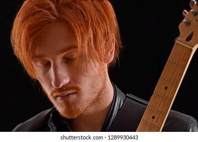 Musician singer artist holding a guitar on black background.