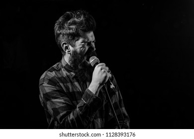 Musician, singer makes effort to win musical contest. Man with tense face holds microphone, singing song, black background. Musician with beard and mustache lighted by spotlight. Talent show concept.