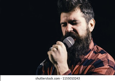 Musician, singer makes effort to win musical contest. Talent show concept. Man with tense face holds microphone, singing song, black background. Musician with beard lighted by spotlight, copy space.