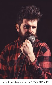 Musician, singer singing in music hall, club. Musician with beard and mustache lighted by spotlight. Vocalist concept. Man with tense strict face holds microphone, singing song, black background.