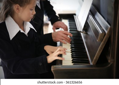 Musician teacher trains to play piano little girl, close up