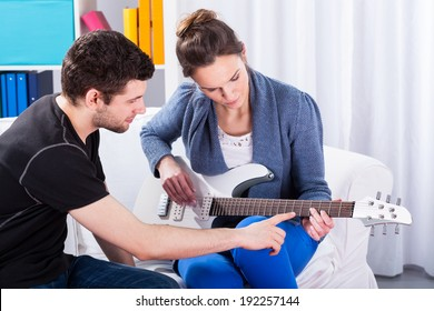 Musician teaching his girlfriend playing electric guitar on a date