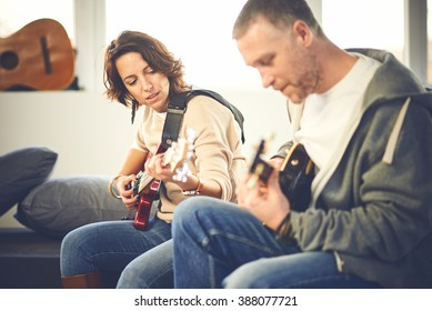 Musician teaching his girlfriend playing electric guitar