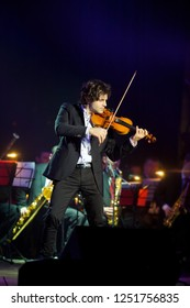 Musician violinist with a violin in his hands standing on stage during the concert. Around the bright light from the floodlights. The orchestra accompanies the musician.