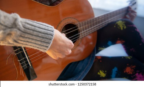 musician woman playing acoustic guitar in bedroom