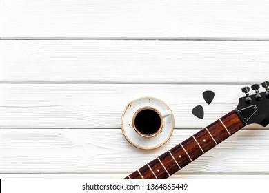 Musician work place with guitar and coffee on white wooden background top view mock up