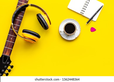 Musician work place with guitar, earphones, notebook and coffee on yellow background top view mock up