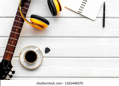 Musician work place with guitar, earphones, notebook and coffee on white wooden background top view mock up