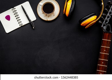 Musician work place with guitar, earphones, notebook and coffee on black background top view mock up