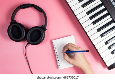 Musician is writing on notebook with studio  pink copy space