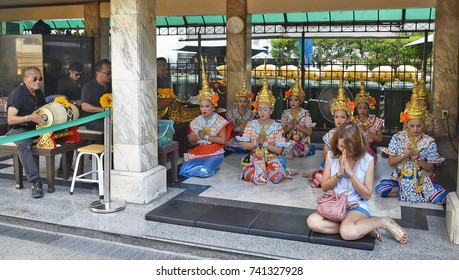 Musicians and dancers at Erawan Shrine in Bangkok. Musicians and dancers playing and dancing for a worshipper at Erawan Shrine in Bangkok, Thailand. May 1st, 2017.
