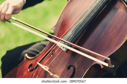 Musician's hands playing violoncello outdoors, closeup