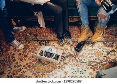 Musicians having rehearsal in home studio. On the floor amplifiers, laptop and headphones.