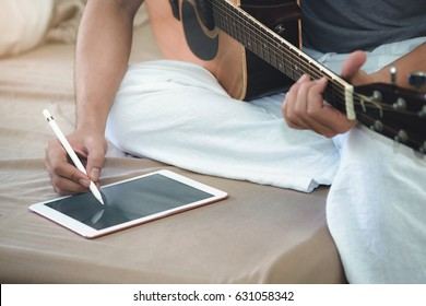 Musicians play guitar and compose songs using the tablet.