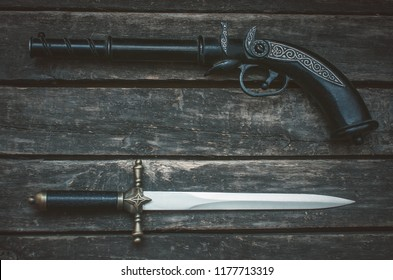 Musket gun and dagger knife on wooden table background with copy space.