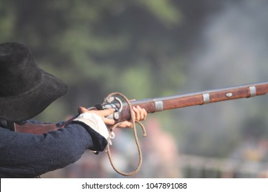 The musketeer in a black broad-brimmed hat fires an old brown musket during the battle at living history event. Re-enactment of the battle of 17th century. Armed man in action. Finger on the trigger.